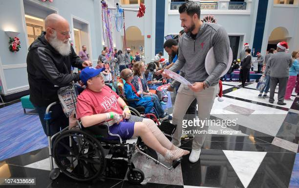 Texas Rangers infielder Joey Gallo signs an autograph for Jace Brewster from Justin Texas during a holiday party for patients at Cook Childrenâs...