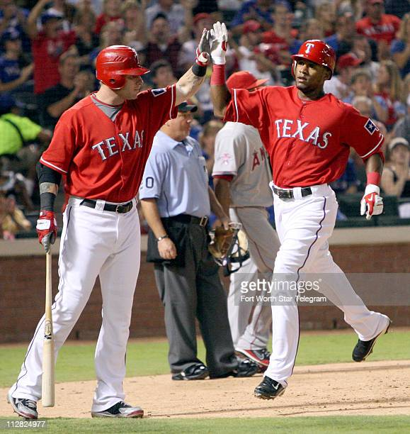 Texas Rangers Josh Hamilton high-fives Julio Borbon after scoring on a sacrifice by Michael Young in the bottom of the fifth against the Los Angeles...