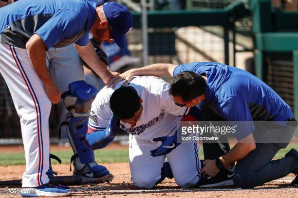 Texas Rangers left fielder Willie Calhoun grabs his face after he's hit by a pitch during the spring training MLB baseball game between the Los...