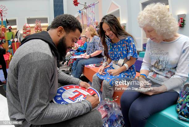 Texas Rangers outfielder Delino Deshields signs an autograph for Savannah Gristina of Fort Worth Texas during a holiday party for patients at Cook...