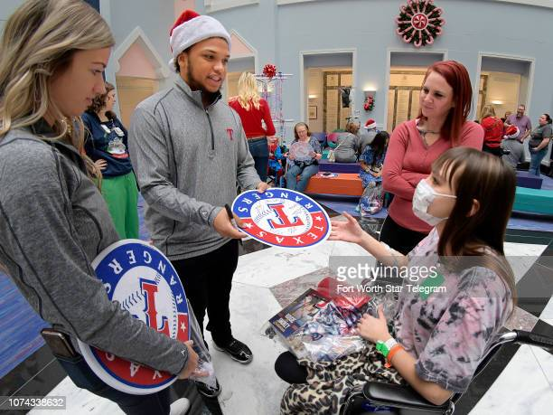 Texas Rangers outfielder Willie Calhoun signs an autograph for Kayleigh Rivera from Denton Texas during a holiday party for patients at Cook...