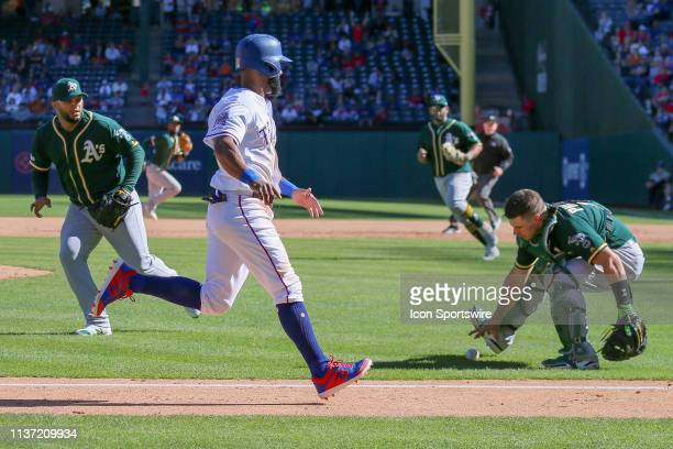 Texas Rangers pinch hitter Danny Santana scores the go ahead run on a squeeze play during the bottom of the 8th inning between the Oakland Athletics...