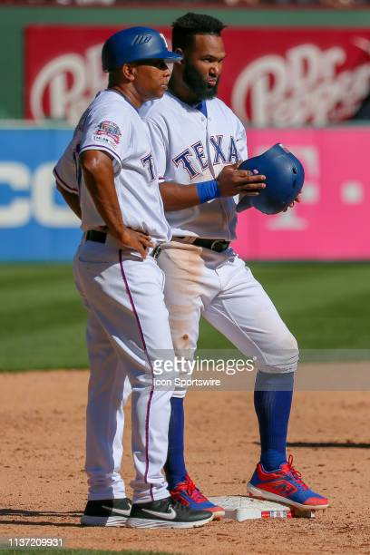 Texas Rangers pinch hitter Danny Santana talks with 3rd base coach Tony Beasley after he hits a bases clearing triple to tie the game between the...