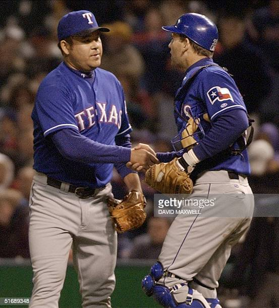 Texas Rangers' pitcher Hideki Irabu is congratulated by catcher Bill Haselman after the final out of the game against the Cleveland Indians 03 May...