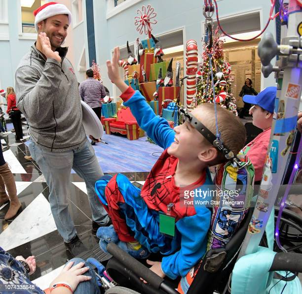 Texas Rangers pitcher Matt Bush gives a highfive to Johnie Barnes from Waco Texas during a holiday party for patients at Cook Children's Hospital in...