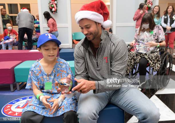 Texas Rangers pitcher Matt Bush talks with Julian Luna from Vernon Texas during a holiday party for patients at Cook Children's Hospital in Fort...