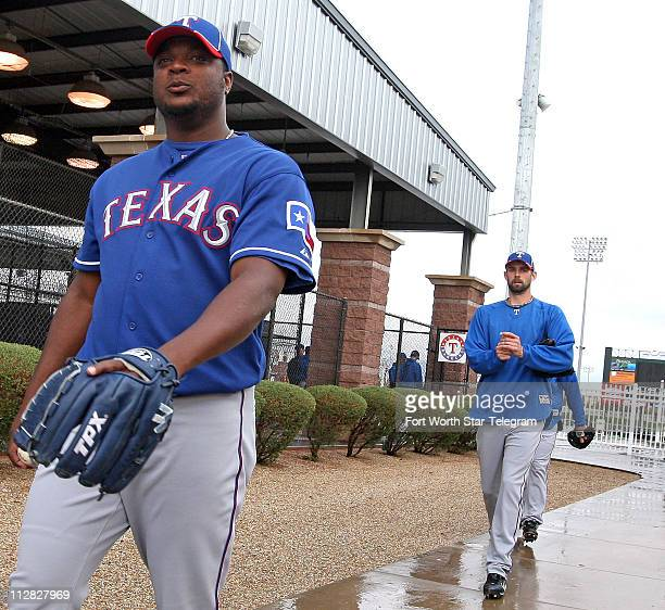 Texas Rangers pitchers Frank Francisco left and Dustin Nippert right walk on the rain soaked sidewalk past the batting cages during spring training...