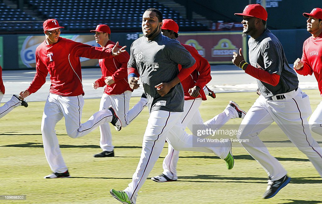 Texas Rangers pitchers including Alexi Ogando, left, and Neftali Feliz, center, run sprints during a pitchers' mini-camp at Rangers Ballpark in Arlington, Texas, on Friday, January 18, 2013.