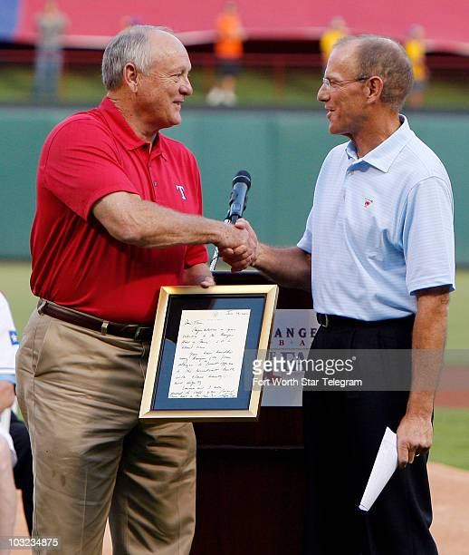 Texas Rangers President Nolan Ryan left presents former Texas Rangers player and current broadcaster Tom Grieve a letter from President George W Bush...