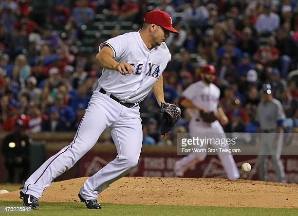 Texas Rangers relief pitcher Shawn Tolleson bobbles a smash by the Kansas City Royals' Mike Moustakas throwing Moustakas out at first base in the...