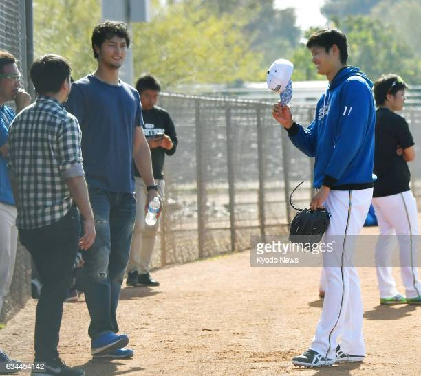 Texas Rangers righthander Yu Darvish chats with Nippon Ham Fighters twoway player Shohei Otani while visiting his former club's training camp in...