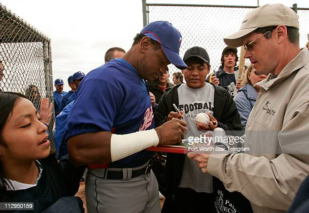 Texas Rangers' Sammy Sosa signs autographs for fans as he makes an appearance during spring training Friday February 23 in Surprise Arizona