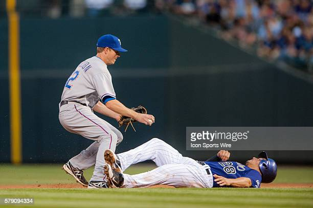 Texas Rangers second baseman Josh Wilson tags Colorado Rockies third baseman Nolan Arenado out on the base path before turning a double play during a...