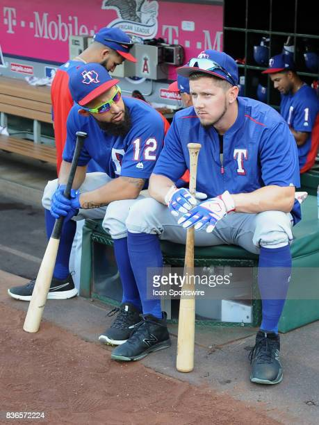 Texas Rangers second baseman Rougned Odor talks with left fielder Ryan Rua while sitting near the dugout during batting practice before a game...