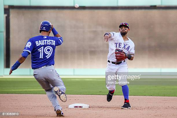 Texas Rangers second baseman Rougned Odor turns a double play as Toronto Blue Jays right fielder Jose Bautista heads towards him during game 1 of the...