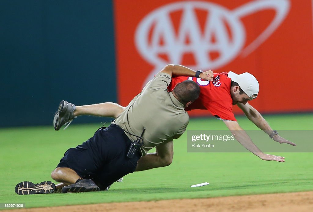 Texas Rangers security guards chase down a fan on the field in the ninth inning against the Chicago White Sox at Globe Life Park in Arlington on August 19, 2017 in Arlington, Texas.