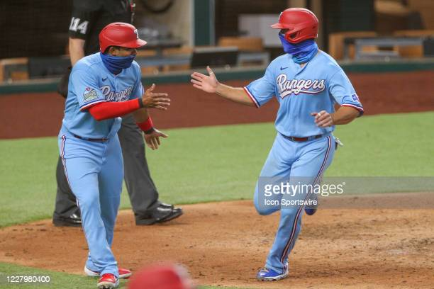 Texas Rangers shortstop Elvis Andrus and catcher Jeff Mathis both score during the 4th inning of the MLB game between the Los Angeles Angels and...