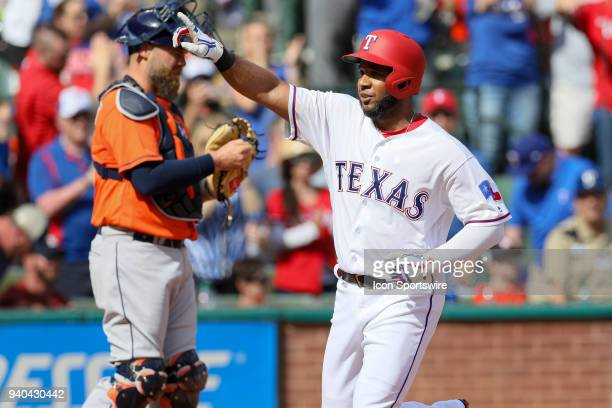 Texas Rangers Shortstop Elvis Andrus gestures as he crosses home plate after hitting a home run during the baseball game between the Houston Astros...