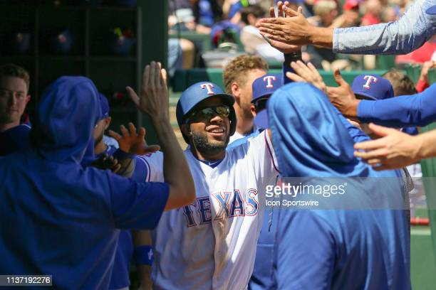 Texas Rangers shortstop Elvis Andrus slaps hands in the dugout after stealing home plate during the game between the Oakland Athletics and Texas...