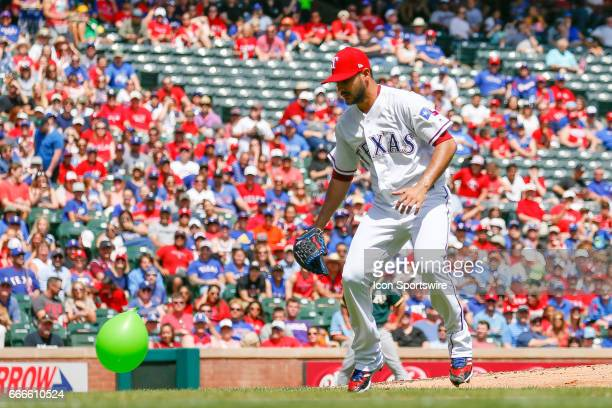 Texas Rangers Starting pitcher Martin Perez fields a balloon that floats towards the mound during the MLB baseball game between the Oakland Athletics...
