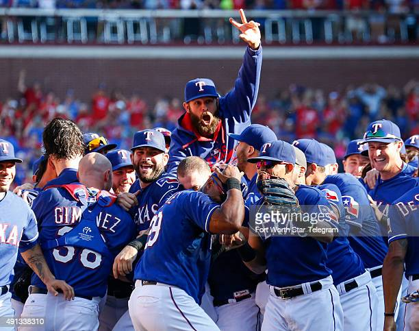 Texas Rangers starting pitcher Nick Martinez, middle top, leaps to celebrate with Rangers teammates following their 9-2 win over the Los Angeles...