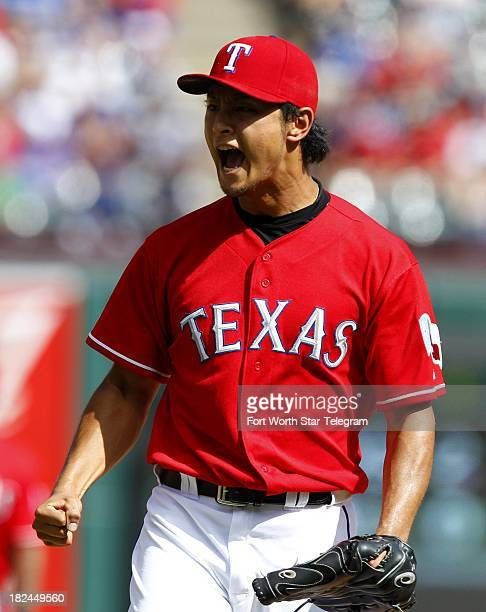Texas Rangers starting pitcher Yu Darvish reacts after striking out the Los Angeles Angels' Hank Conger in the fifth inning at Rangers Ballpark in...