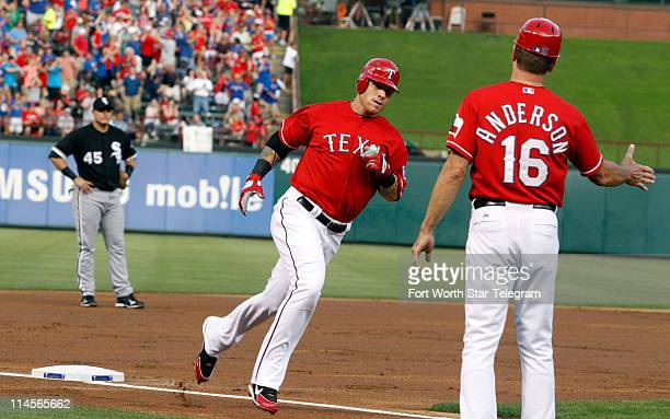 Texas Rangers third base coach Dave Anderson greets Josh Hamilton who rounds the bases after hitting a homer in the first inning against the Chicago...