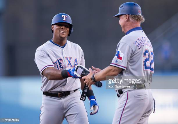 Texas Rangers third baseman Adrian Beltre hands gear off to Texas Rangers first base coach Steve Buechele after getting on first during the game...