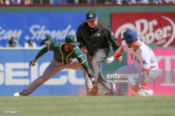 Texas Rangers third baseman Patrick Wisdom beats the tag by Oakland Athletics shortstop Jurickson Profar during the game between the Oakland...