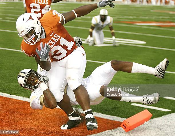 Texas running back Cody Johnson drags Central Florida defensive back Justin Boddie into the end zone for a touchdown at Texas Memorial Stadium in...