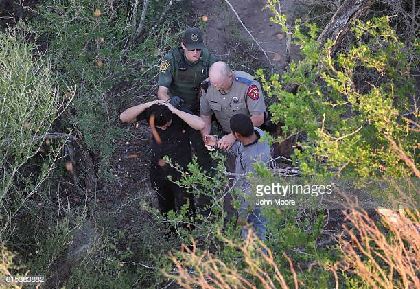 Texas state trooper and a US Border Patrol agent detain undocumented immigrants on October 18 2016 near McAllen Texas Immigration and border security...
