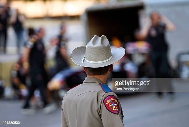Texas State Trooper looks on as former Formula One driver David Coulthard of Great Britain prepares to pilot the Red Bull Show Car in front of the...