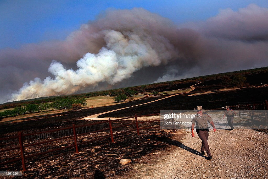 Texas State Troopers Aaron Lewis and Greg Sullivan open a gate to allow livestock to escape a running wildfire on April 19, 2011 in Graford, Texas. Dozens of area homes have been destroyed in the wildfires that have been fueled by dry conditions, high winds, and low humidity.