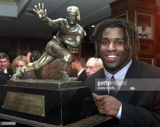 Texas tailback Ricky Williams winner of the 1998 Heisman trophy poses with US college football's highest honor 12 December at the Downtown Athletic...