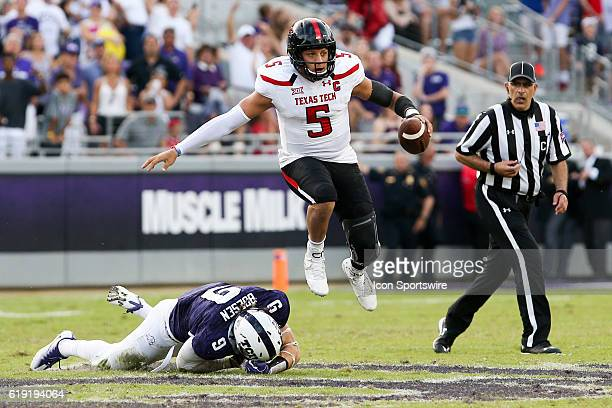 Texas Tech Red Raiders quarterback Patrick Mahomes II leaps over an outstretched tackle attempt by TCU Horned Frogs defensive end Mat Boesen during...