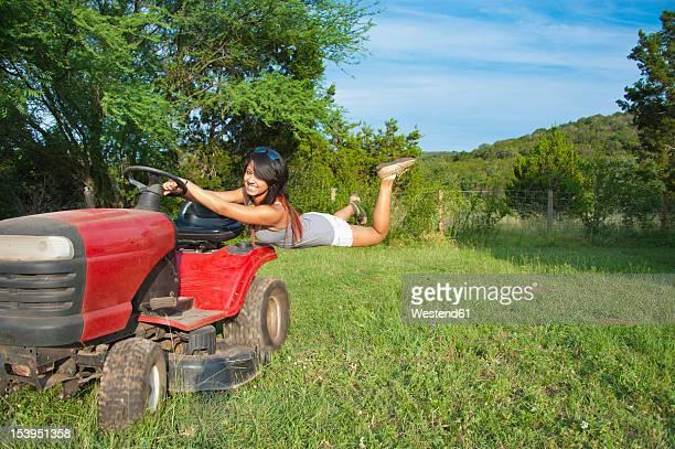 USA, Texas, Teenage girl hanging on tractor, smiling