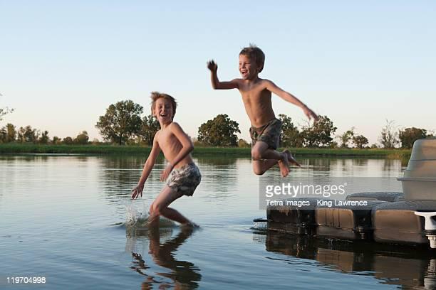 usa, texas, texarkana, two boys (8-9) jumping into lake - only boys stock photos and pictures