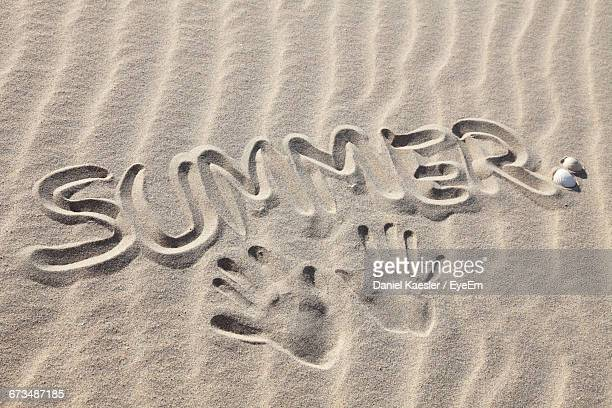 Text And Handprints On Sand At Beach