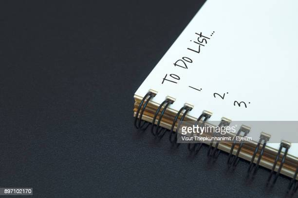 Text And Numbers On Spiral Notebook Over Black Background