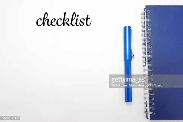 Text By Spiral Book And Pen On White Background