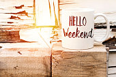 text HELLO weekend on cup of aromatic coffee on wooden cube