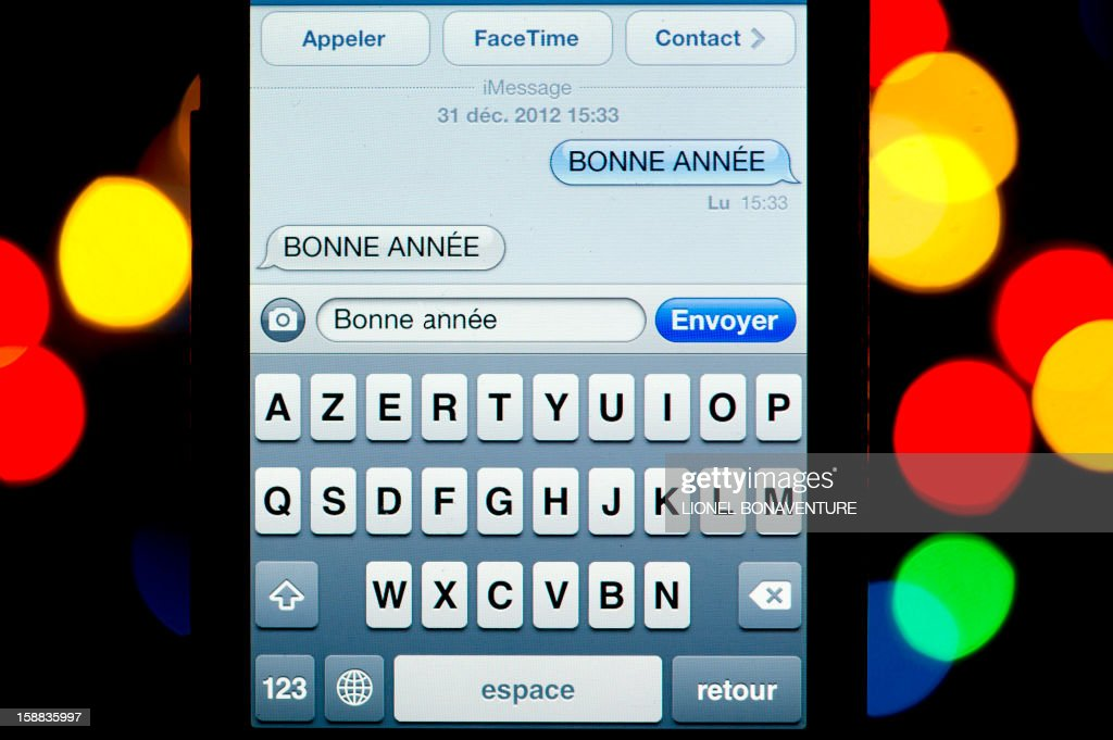 A text message (SMS) of New Year greetings in French is pictured on a smartphone on December 31, 2012 in Paris. Millions of SMS should be sent in the world on January 1, 2013.