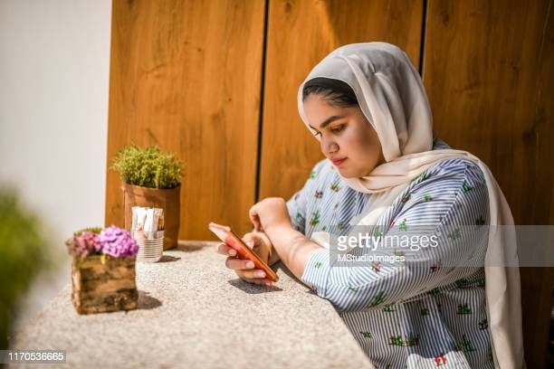 text messaging. - arab women fat stock pictures, royalty-free photos & images