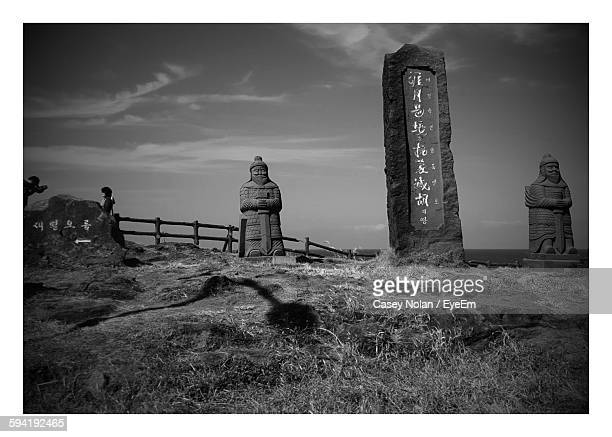 text on rock with stone statues on field against sky - casey nolan stock pictures, royalty-free photos & images