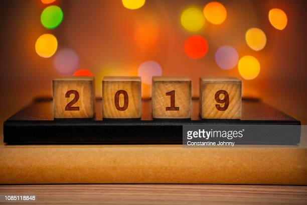 2019 text on wood block against abstract colorful illuminated defocused bokeh lights background. - countdown stock pictures, royalty-free photos & images