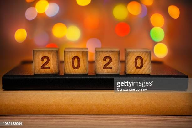 2020 text on wood block against abstract colorful illuminated defocused bokeh lights background. - happy new year 2020 stock photos and pictures