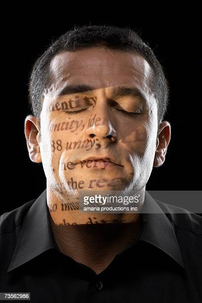 Text projected on man's face, eyes closed