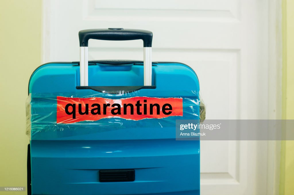 Text Quarantine over suitcase. Concept of flights cancellation, travel restrictions due to coronavirus pandemic : Foto stock