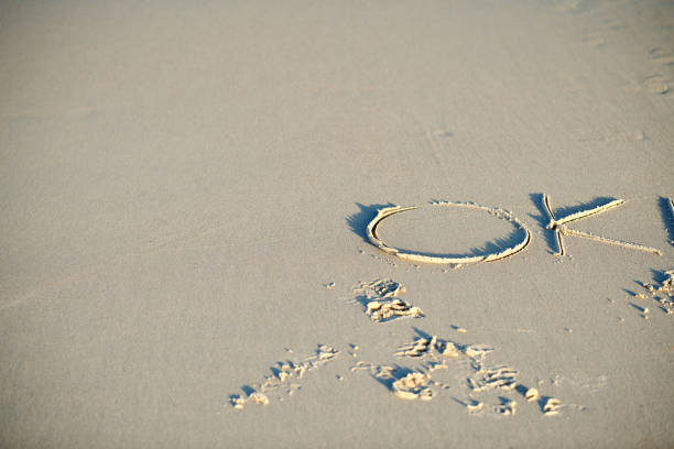 OK text scratched on a beach sand