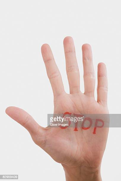 Text STOP written on a person's palm